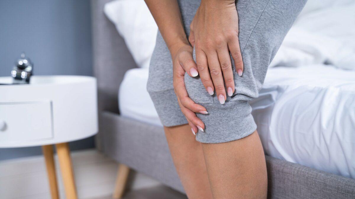 Kobieta trzymająca się za bolące kolano po zerwaniu więzadła krzyżowego przedniego.